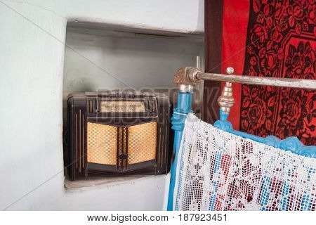 Old retro radio. In the frame there is an old iron blue bed and a red carpet. White background.
