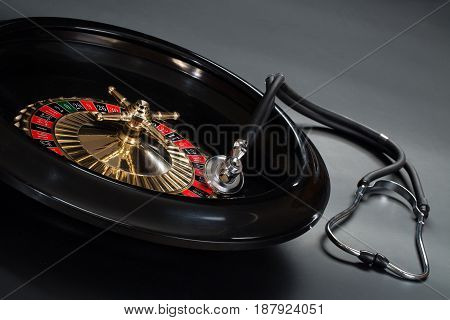 Stethoscope lying on the roulette wheel on the table