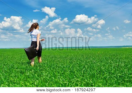 Business woman walk on green grass field outdoor and relax under sun. Beautiful young girl dressed in suit resting, spring landscape, bright sunny day