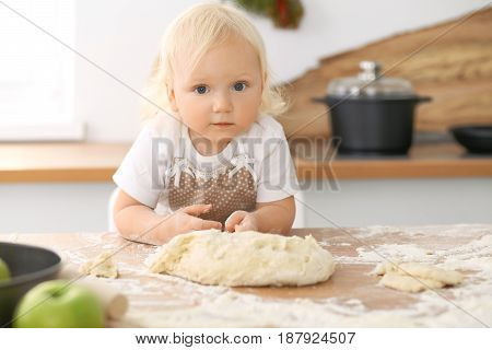Happy family in the kitchen. Mother and child daughter cooking holiday pie or cookies for Mothers day, casual lifestyle photo series in real life interior