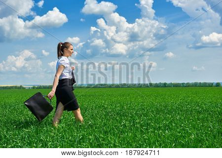 Business woman walk on green grass field outdoor. Beautiful young girl dressed in suit, spring landscape, bright sunny day