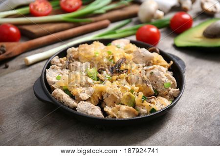 Delicious chicken casserole meal in pan with vegetables on table