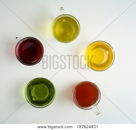 Cups of different tea on white background
