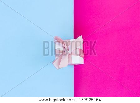 Gift box with pink ribbon on pink and blue background