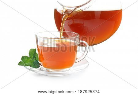 Pouring black tea into glass cup from teapot on white background