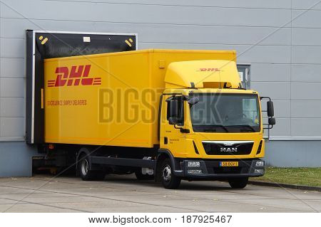 Almere, The Netherlands - May 24, 2017: DHL delivery truck at a loading dock. Nobody in de vehicle.