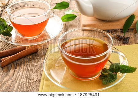 Cups of black tea with mint leaves on wooden table