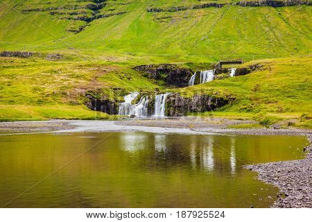 Cascading waterfall Kirkjoufellfoss is reflected in a large puddle at the foot of the mountain Kirkjoufell. Summer in Iceland. Concept of exotic and extreme tourism