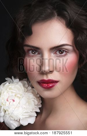 Young beautiful woman with white peony