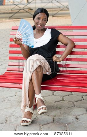 young woman sitting on a red bench is blowing with a fan.