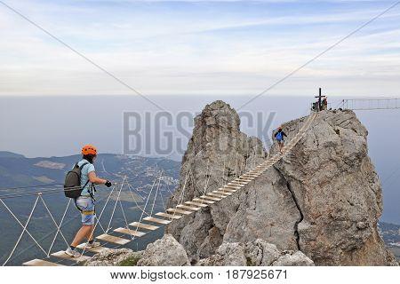 Tourists walk on the hanging bridge between rocks in Yalta Russia