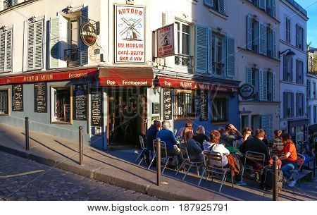 PARIS , France- May 21, 2017: View of typical French cafe Au tour du moulin in Paris. Montmartre area is among most popular destinations in Paris, Au tour du moulin is a typical cafe.