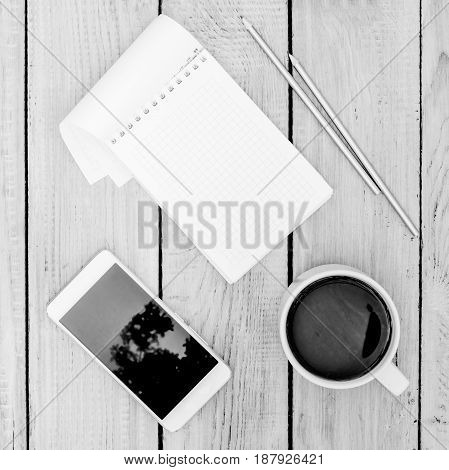 Cup of coffee notepad and phone on the white wooden table