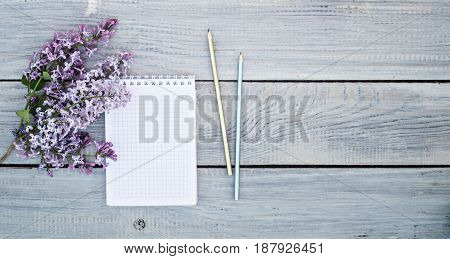 Notepad and a lilac branch on the white wooden table