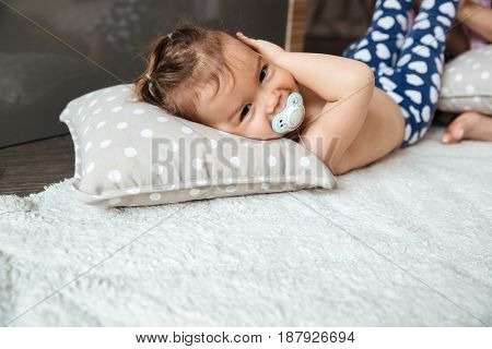 Picture of cute little girl child indoors with nipple lies on bed. Looking at camera.
