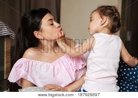 Picture of happy young mother have fun with her little daughter indoors. Looking aside.