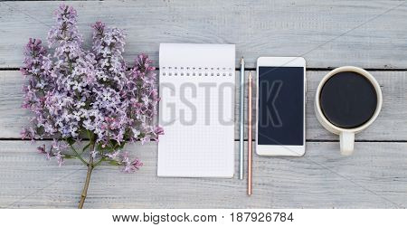 Cup of coffee notepad phone and a lilac branch on the white wooden table