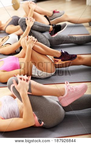 Picture showing young women doing sit-ups in a gym