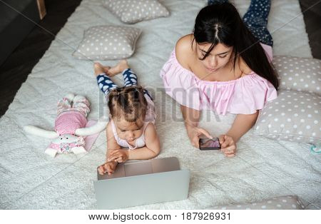 Picture of concentrated young mother chatting by phone while her little daughter lies on bed indoors using laptop computer. Looking aside.