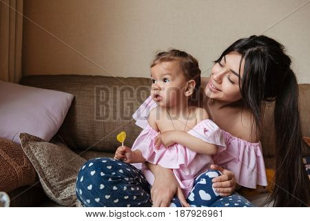 Image of happy young mother sitting on sofa with her little daughter indoors. Looking aside.