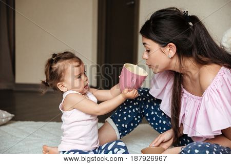 Picture of pretty young mother drinking tea with her little daughter sitting on bed indoors. Looking aside.