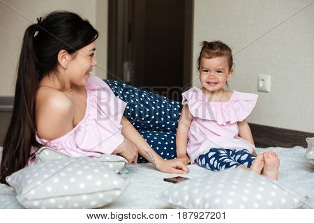 Image of smiling young mother with her little daughter lies on bed indoors. Looking aside.