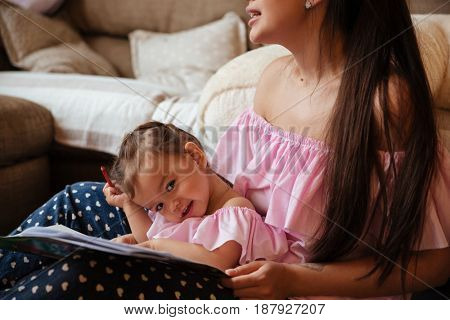 Image of young mother with her little daughter sitting on floor indoors drawing in colouring book. Looking aside.