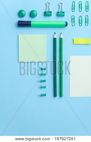 Top view image of office supplies on the blue background table