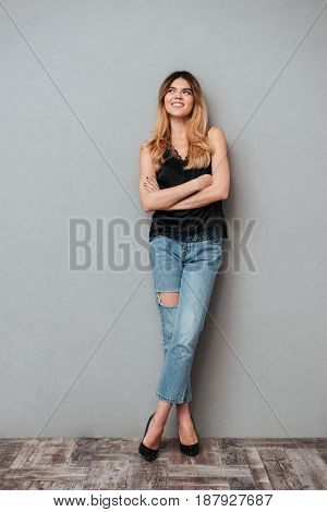 Young woman with folded hands smiling and looking away isolated over grey