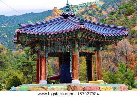 Buddhist Peace Bell surrounded by a rural forest in the Sierra Nevada Mountains, CA