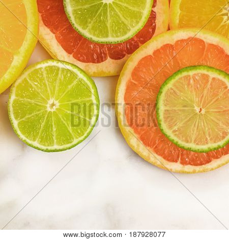Vibrant juicy citrus fruits on a white marble texture with copy space. Grapefruit, lime, and orange slices, square photo