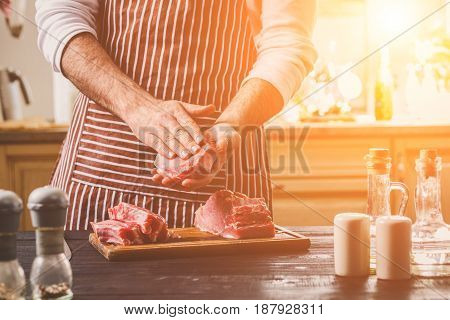 Preparation of dinner. Cooking, processing of meat beef, tenderloin . Person man's hands marinates meat - sprinkles with salt, pepper. Black wooden table, spices and herbs in the frame.