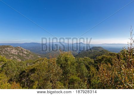 Beautiful view from Round Mt scenic Lookout on Olivers Road at Mount Roland Regional Reserve, Afternoon misty view of moon above green mountain ranges in Tasmania, Australia