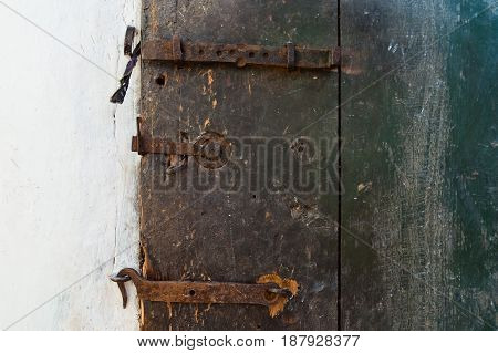 The old door is blue - green, closed to the old bolt and hook.
