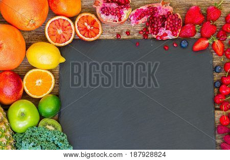 Fresh fruits and berries summer food frame with copy space on black stone