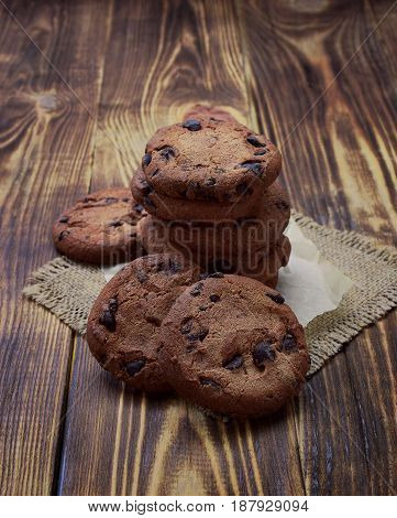 Freshly baked chocolate chip cookies On an old wooden background.