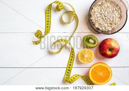 Fitness concept with fruit, bowl of oatmeal and centimeter. Top view background concept. Copy space