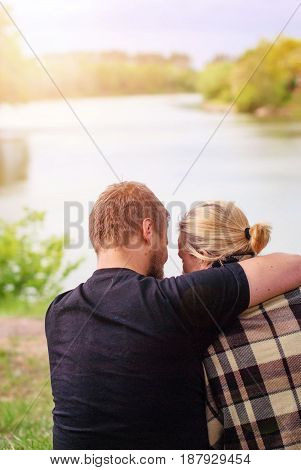A married couple in a plaid sitting hugging on the lake shore. A loving couple hugs in a rug. A man with a beard and a blond woman are sitting hugging each other. The girl and the boy are hugging.