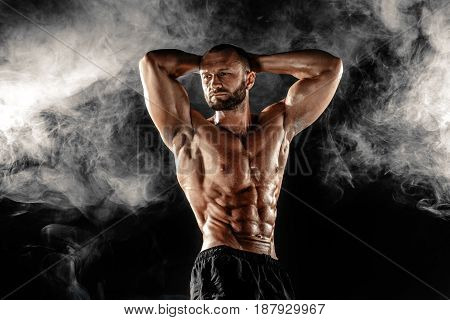 Studio portrait of topless muscular sportsman posing with arms on head over smoke black background.