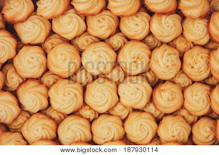 Background texture of small cookies in the shape of flowers.