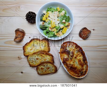 a meal on the wooden table decorate with pine cone an d bale fruits. Flat Lay Garlic bread Gratin Salad