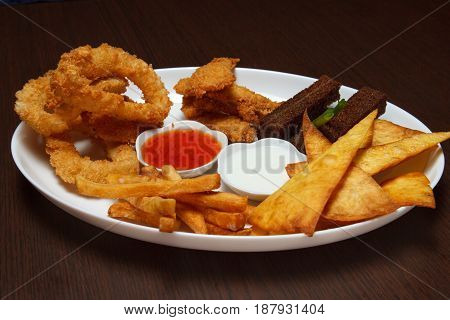 White plate with appetizers in a bar on the background of a wooden table