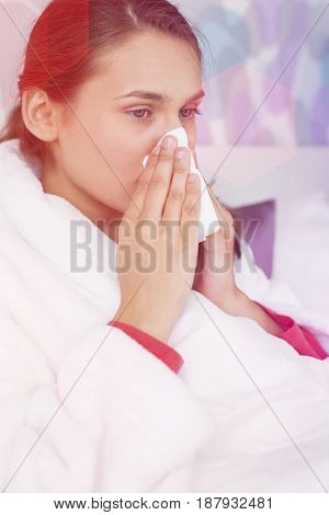Young woman suffering from cold blowing nose in bedroom