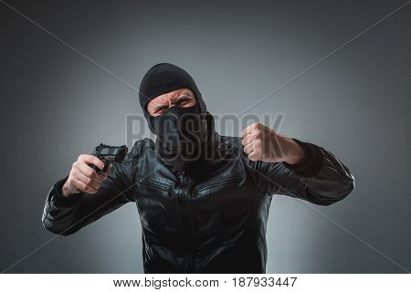 Masked robber with gun, looking into the camera. Studio shot on gray background. Emotions