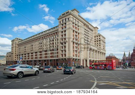 Moscow Russia - May 13 2017: Urban view on the Four Seasons hotel the tourist bus and cars moving down the street Okhotny Ryad in the center of Moscow
