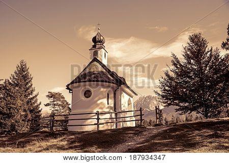 idyllic chapel in the bavarian alps sepia toned