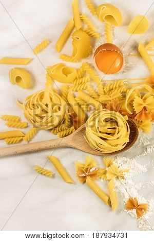 Various types of pasta on a white marble table with an egg and flour, forming a frame for text