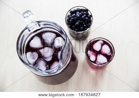 Blueberry juice in a decanter and a glass next to frozen berries