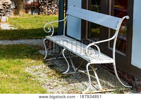 The White park bench in the sun in the garden