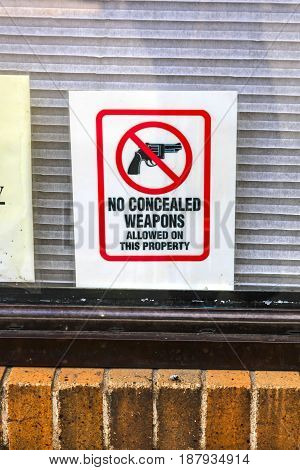 Butte, Montana, USA - 07/21/2015: No Concealed Weapons placard in the window of a store in Butte Montana